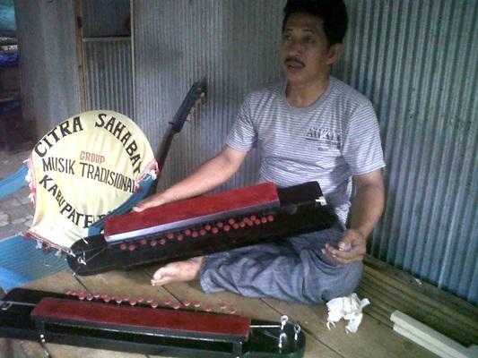 Patahuddin dengan dua alat musik Mandali buatannya (foto: mfaridwm)