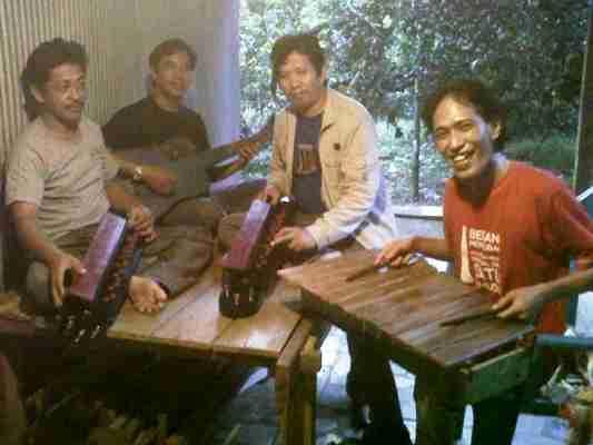 Patahuddin bersama tiga orang tamunya,termasuk penulis saat mencoba alat musik tradisional buatannya (foto: subhan)