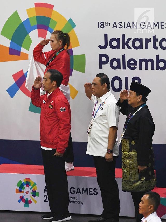 Presiden RI Joko Widodo dan Ketua PB IPSI, Prabowo Subianto melakukan penghormatan kepada bendera merah putih saat seremoni penyerahan medali emas kepada Atlet Pencak Silat Indonesia. (foto: dok. inasgoc)