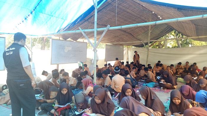 Para relawan pendidikan mengajar di sekolah darurat. (foto: ist/palontaraq)