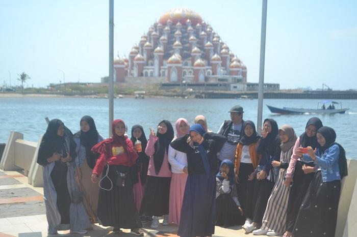 Berfoto dengan latar belakang Masjid 99 Kubah dari Pelataran Pantai Losari. (foto: ist/palontaraq)