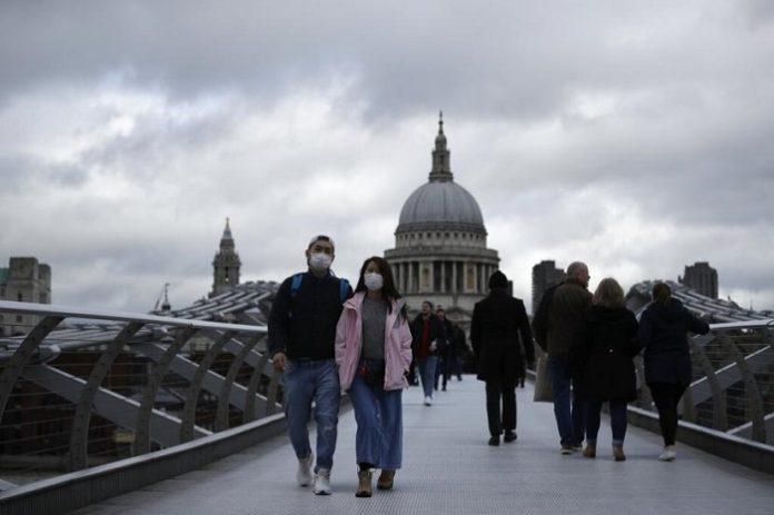 Sejumlah orang berjalan di Millenium Bridge dengan latar Katedral St Paul di London, Inggris, Selasa (10/3). Jumlah kematian akibat virus corona di Inggris mencapai enam orang.(AP Photo/Matt Dunham)