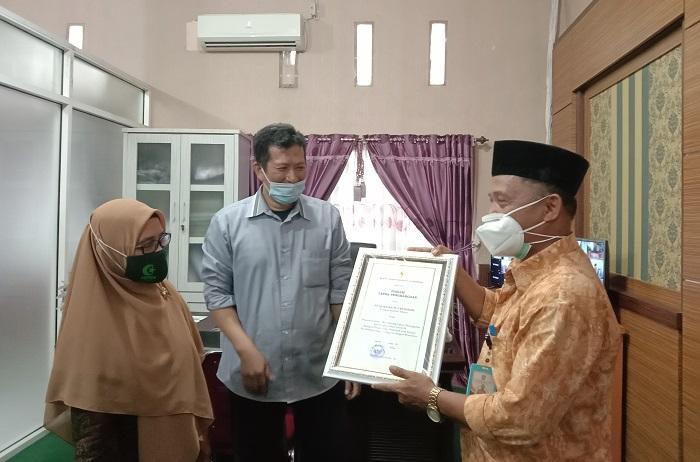 Penyerahan Penghargaan Menkes RI diserahkan oleh Kadis Kesehatan Pangkep, Frans Manaba kepada Ketua YASDIC IMMIM Pangkep, Dra Hj Sri Hajati Fachrul Islam di ruang kerjanya. (foto: ist/palontaraq)